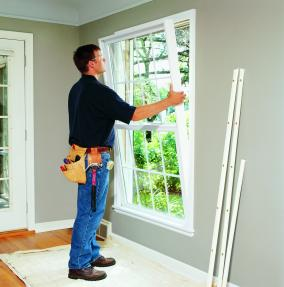 Installer inserting window into house opening